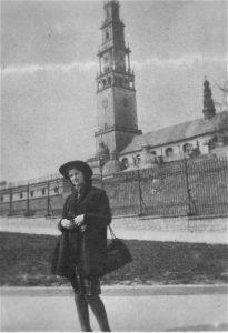 לאה המרשטיין ליד מנזר יאסנה גורה בצ'נסטוחובה, לבושה במקטורן ובכובע שקיבלה מטוסיה אלטמן (ספטמבר, 1943)
