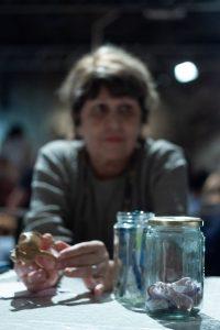 אישה מבוגרת ליד צנצנות זכוכית