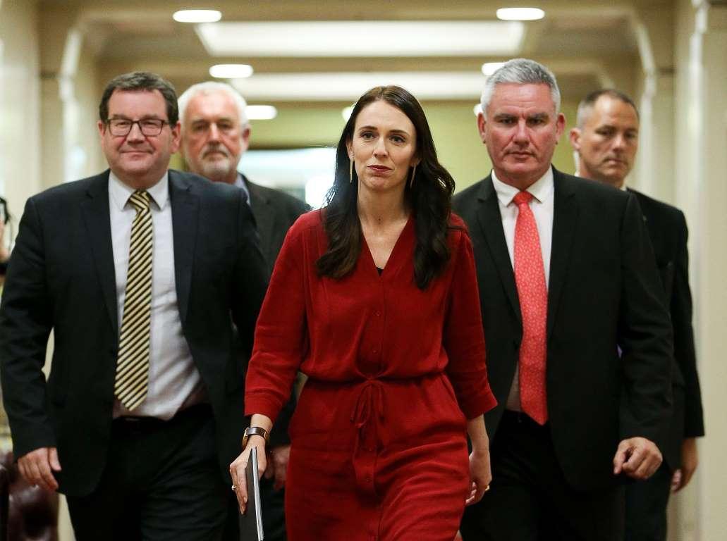 ג'סינדה ארדרן ראשת ממשלת ניו זילנד, נושא הכתבה, צועדת ומאחוריה הגברים בצוות שלה