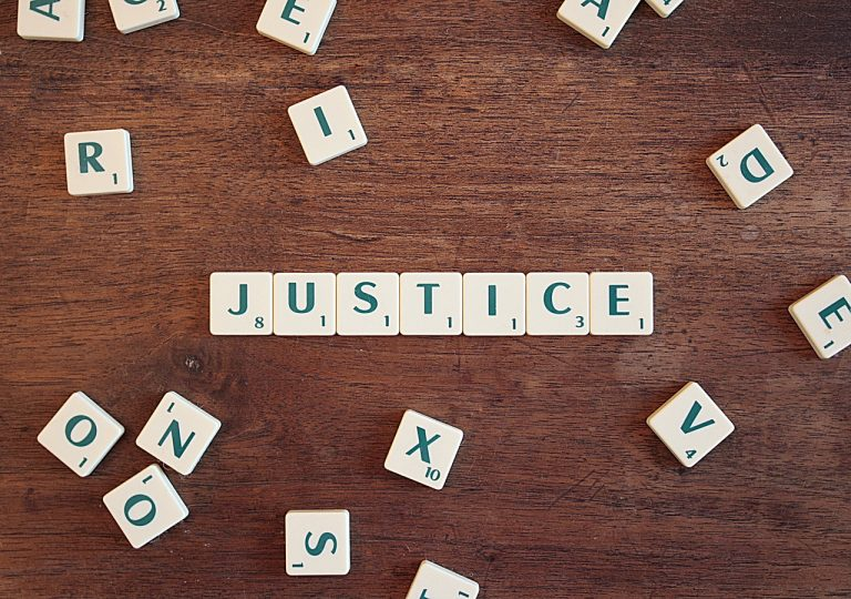 """הכיתוב """"צדק"""" על חלקי שבץ נא באנגלית שואל את שאלת הכתבה: מי האשם באונס?"""