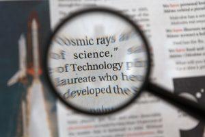 זכוכית מגדלת שמראה טקסט טכנולוגי מדעי ומסמנת את הסדר הפטריארכי שיעלה לאחר משבר הקורונה