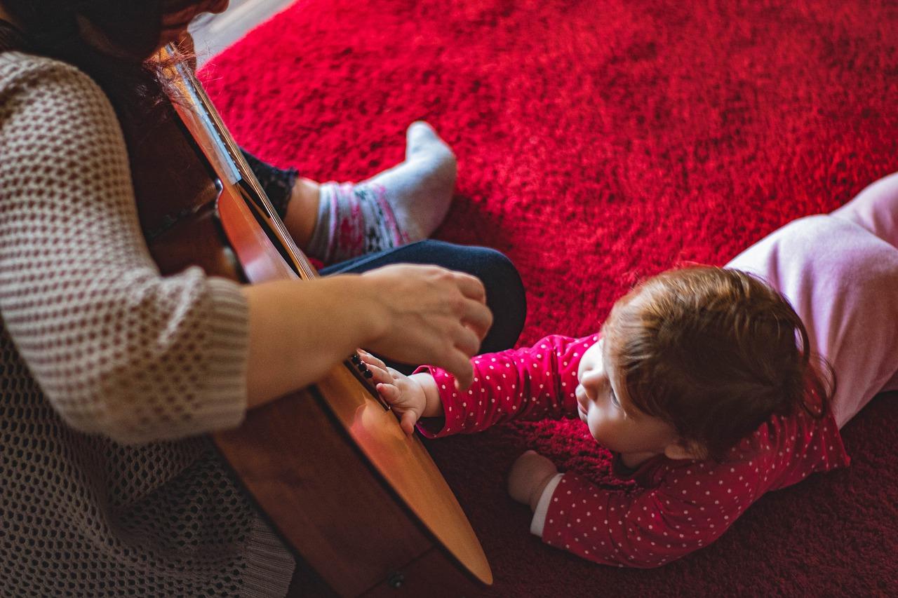 אמהות מוזיקאיותתמונה של אמא מחזיקה גיטרה ותינוק לידה