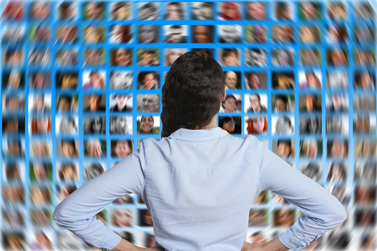 קהילות נשים וירטואליות מיוצגות בתמונה של אישה מול מסכים עם פרצופים