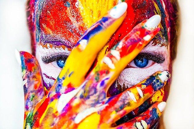 אישה מכוסה צבעים מייצגת מטפלות באמנות